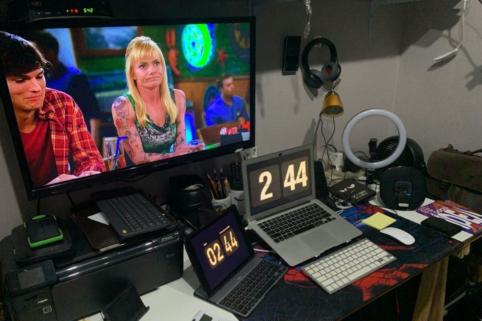 Foto da mesa de trabalho em casa do Uri Barros. Notebook e tablet, ambos com teclados externos; ao fundo, uma TV. Mesa com bastante coisa em cima.