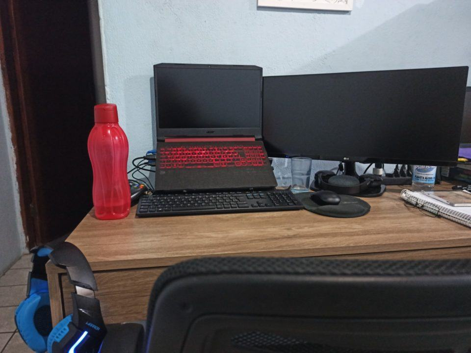 Escritório doméstico atualizado do Henrique Bispo, com nova mesa, computador, teclado e fones de ouvido.