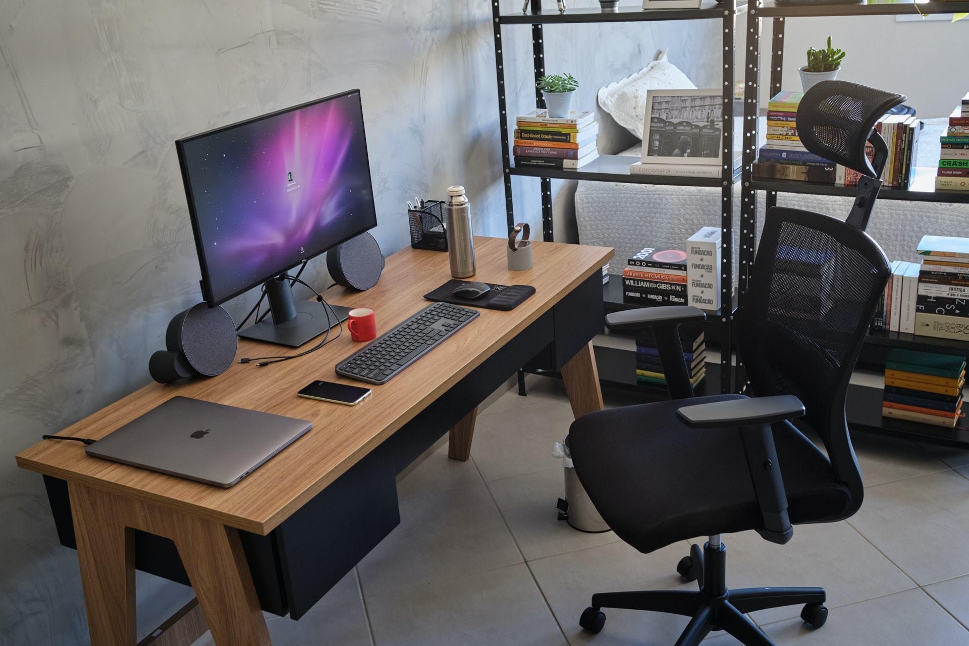 Foto de lado de uma mesa de trabalho, com notebook, monitor grande, teclado, mouse e outros objetos sobre ela. Poltrona à vista e, ao fundo, uma estante vazada.