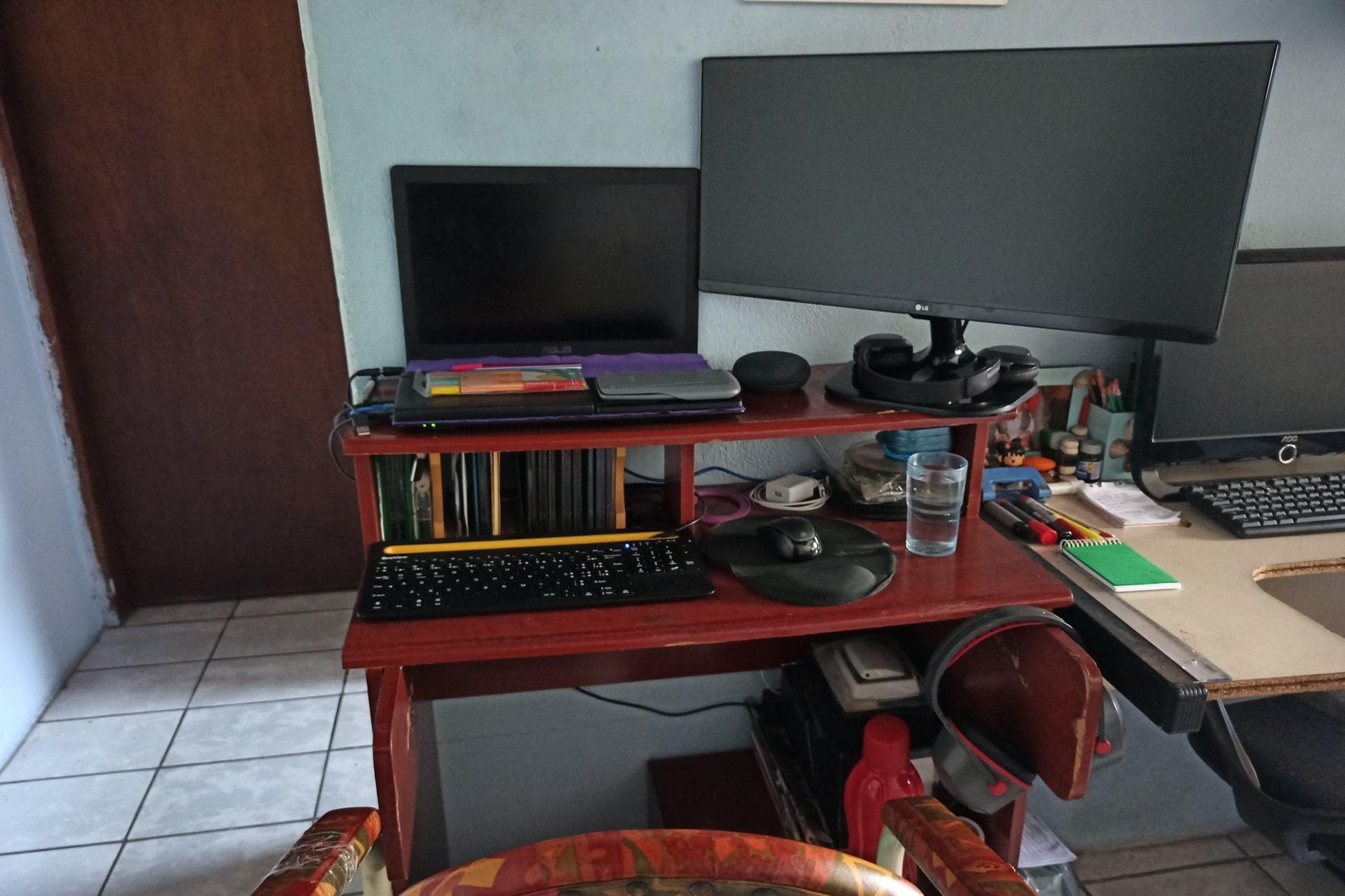 Escritório doméstico do Henrique Bispo, mostrando um rack com notebook, teclado e mouse; um monitor grande e alguns objetos.