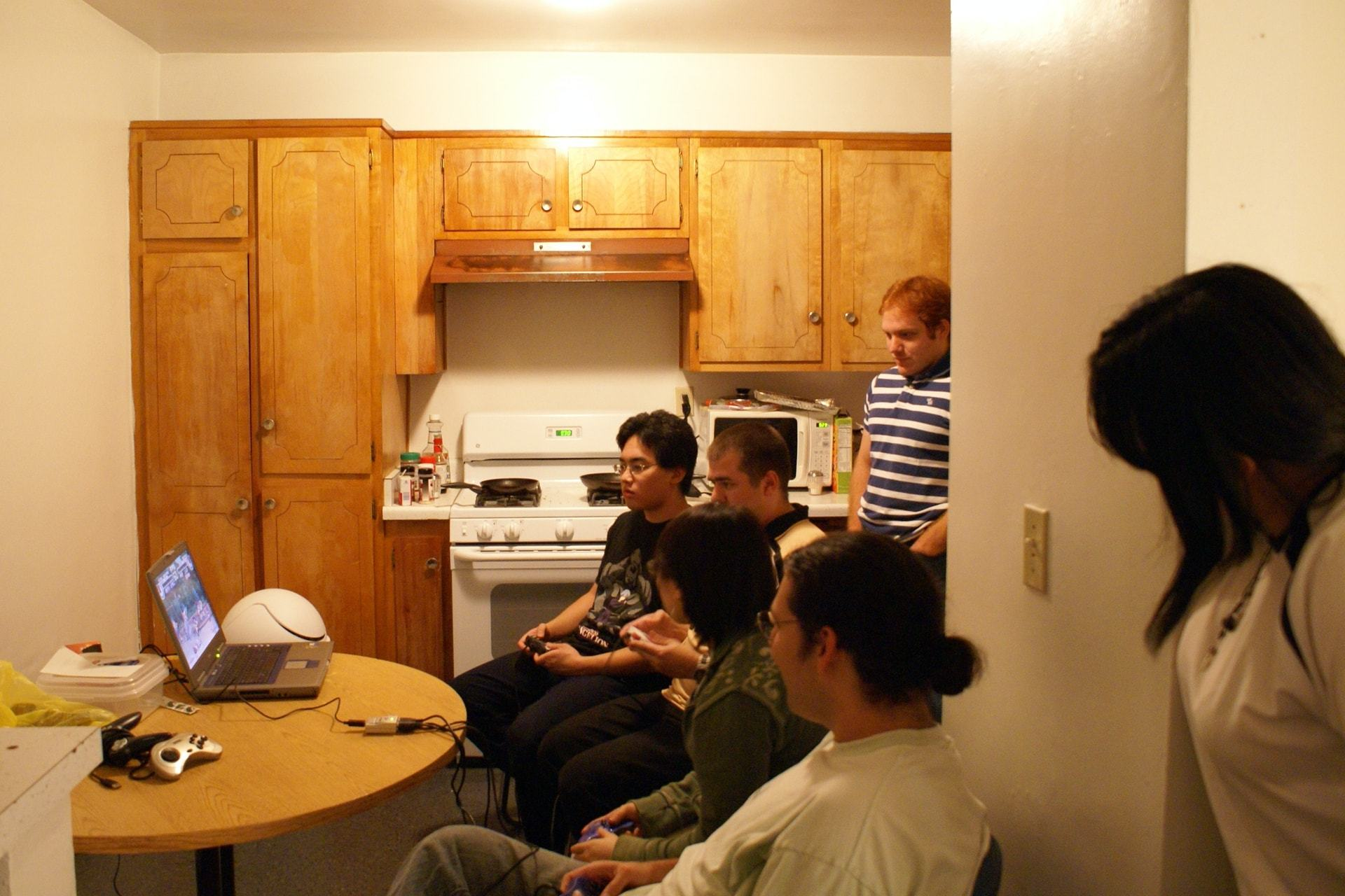 Pessoas jogando video game em um notebook velho em uma cozinha.