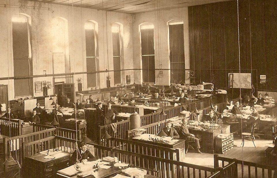 Visão panorâmica de um escritório antigo, com dezenas de homens em suas mesas e uma mulher apenas. Pé direito alto, foto em sépia.