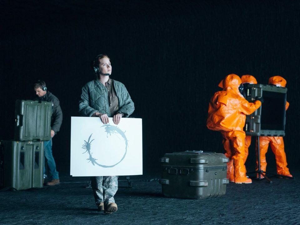 Mulher em primeiro plano segurando um cartaz com um círculo. À esquerda, homem ao fundo. À direita, três pessoas com roupas de proteção laranjadas. Todos dentro de uma caverna.