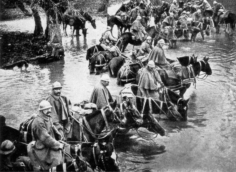 Foto em preto e branco de soldados montados em cavalos dentro de um rio.