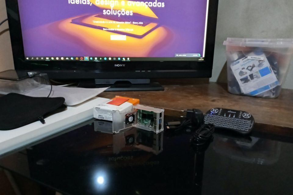 """Mini-teclado e objeto não identificado sobre a mesa lateral (em """"L"""") na bancada do Fernando. Ao fundo, a TV Sony em destaque."""