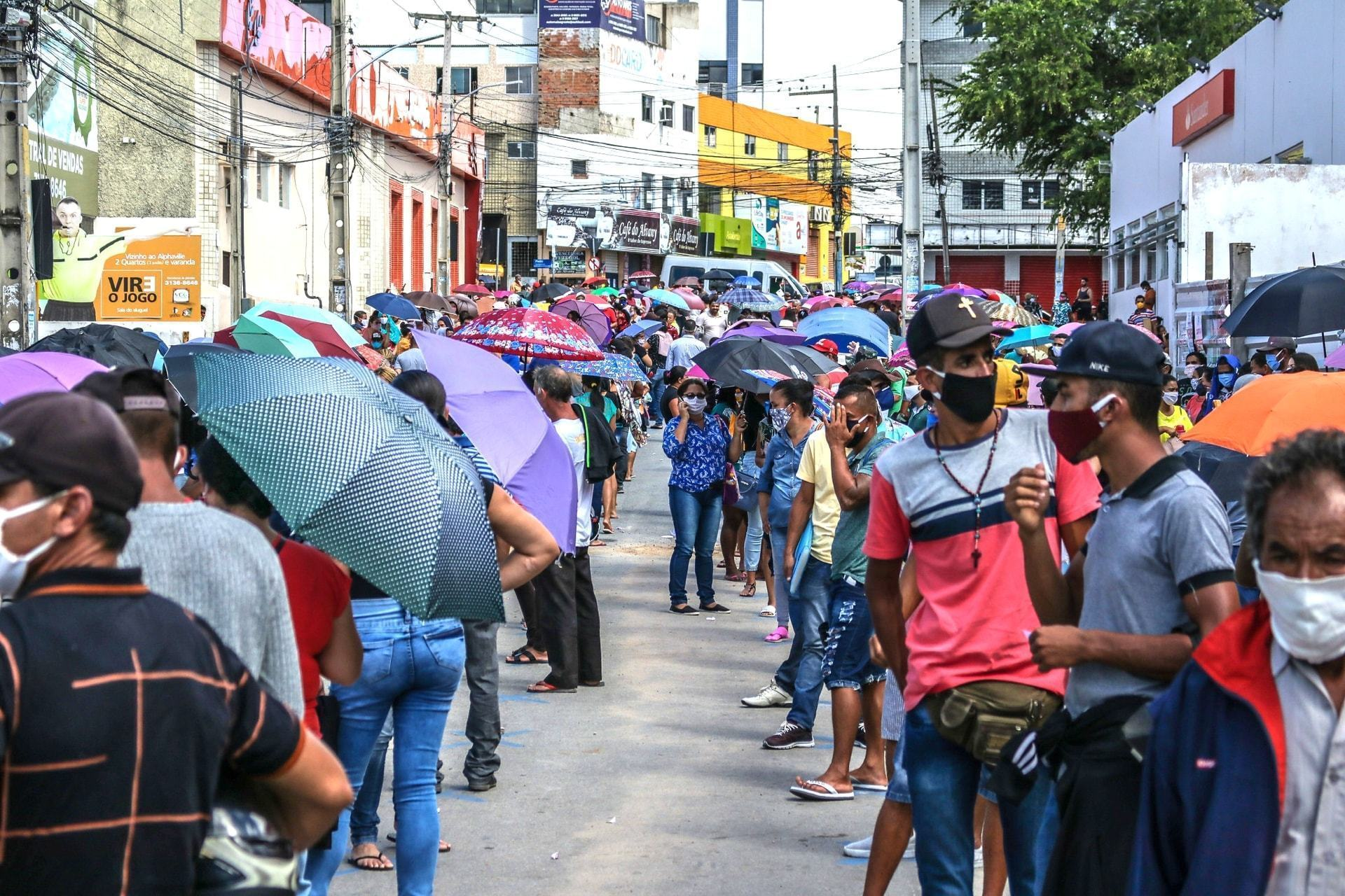 Pessoas de máscara e segurando guarda-chuvas em uma grande fila no meio da rua.