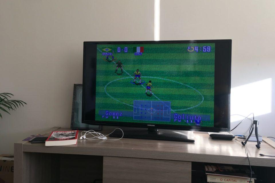 """Foto de uma TV sobre um rack, com livros espalhados e, do lado direito da TV, um roteador e o Raspberry Pi. Na tela, cena do jogo """"International Super Star Soccer Deluxe"""", do Super Nintendo."""