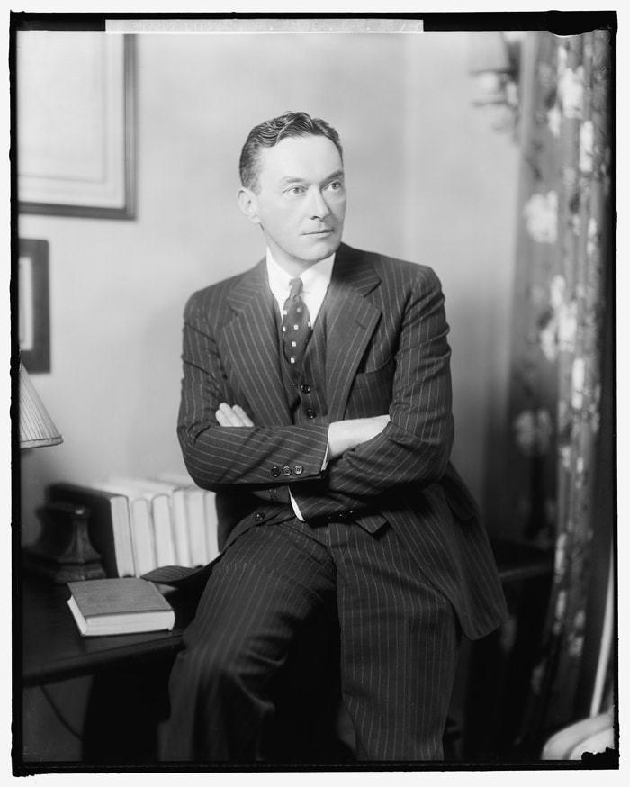 Walter Lippmann, de terno, sentado em uma mesa. Foto em preto e branco.