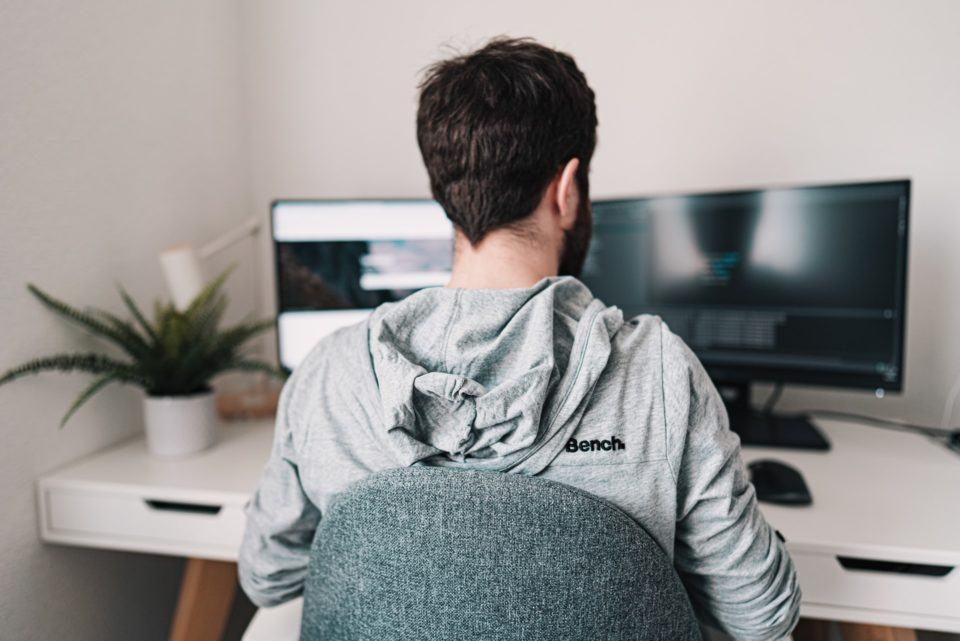 Homem com blusa, sentado em uma cadeira, com um computador com dois monitores à sua frente.