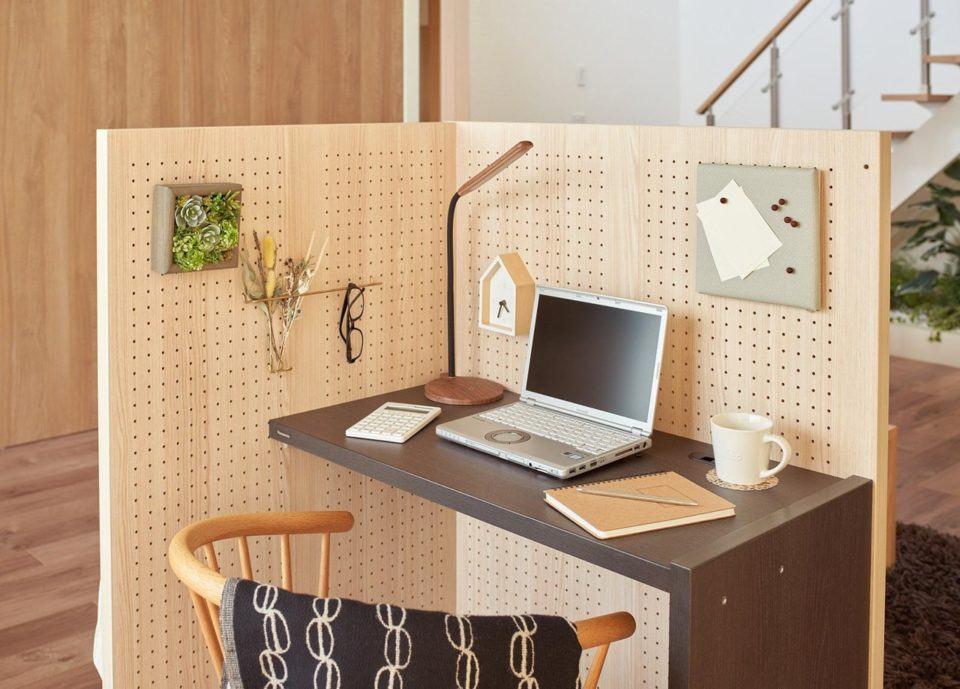 Foto da parte interna do cubículo, com notebook e objetos sobre a mesinha, e outras coisas penduradas nos furos das paredes.