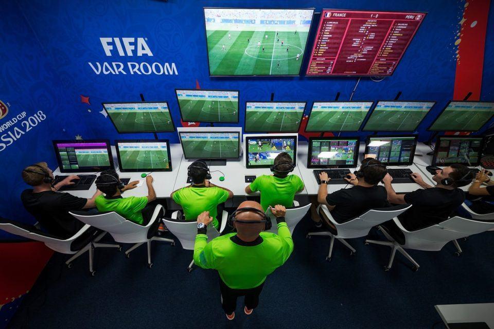 Foto, de cima, de uma central do VAR em jogo da Copa do Mundo. Várias telas com árbitros à frente. De pé, atrás deles, outro árbitro supervisiona a situação.