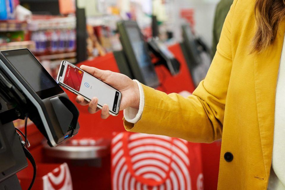 Mulher segurando um iPhone com o Apple Pay aberto, aproximando-o de um terminal de pagamento.