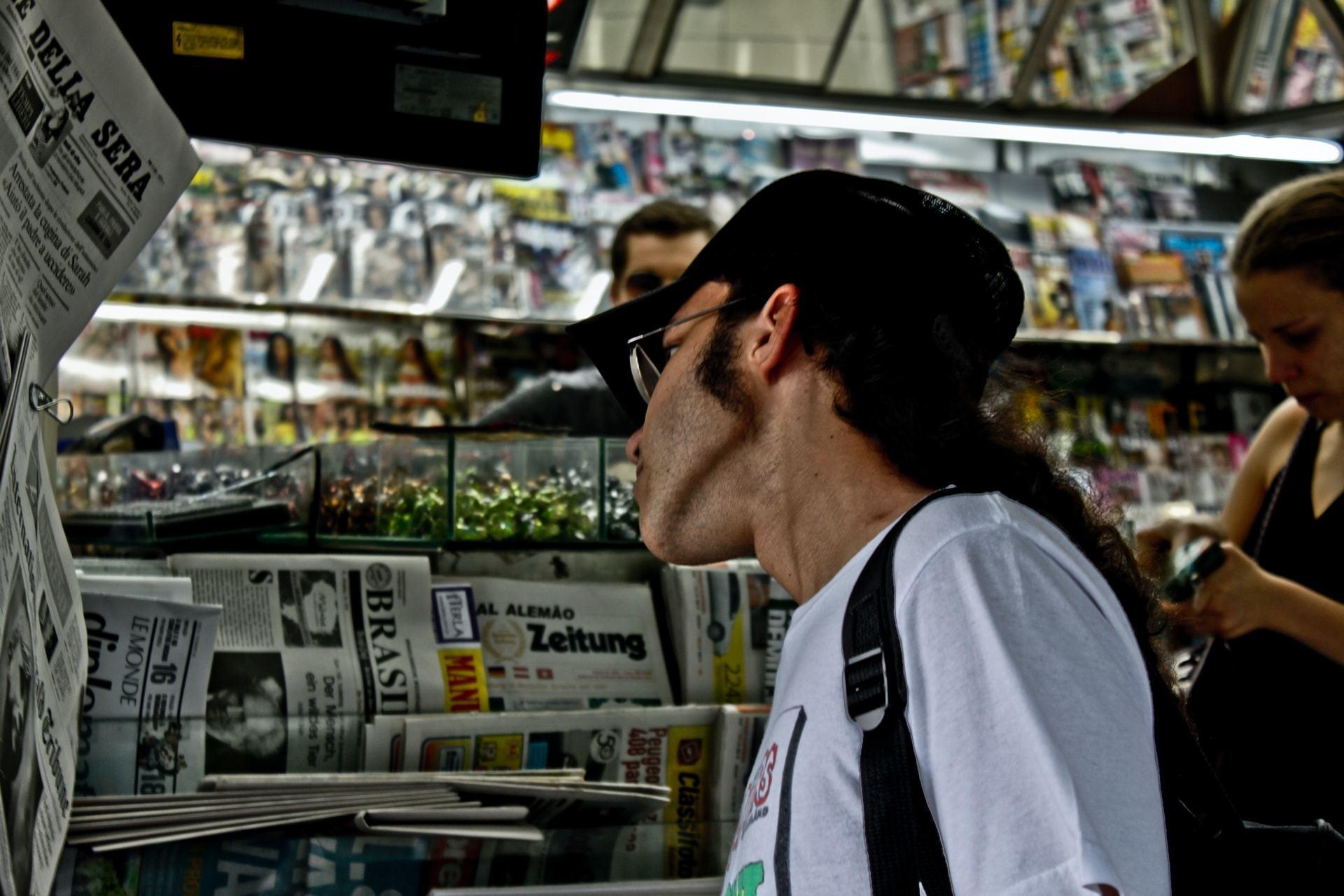 Homem de boné, barba e óculos, de lado, olha jornais pendurados na parede de uma banca.