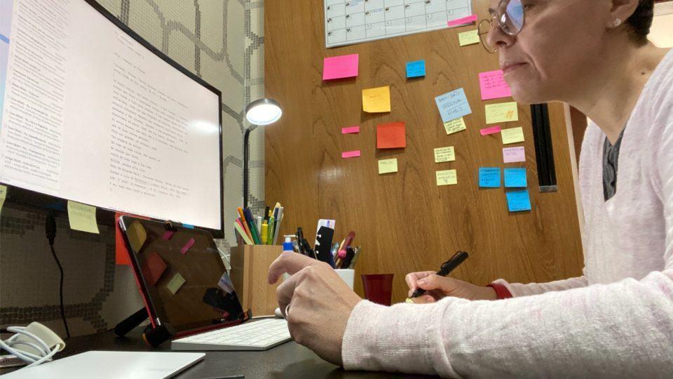 Foto lateral da Laura (no canto direito da tela) trabalhando em frente ao monitor, do outro lado do enquadramento.