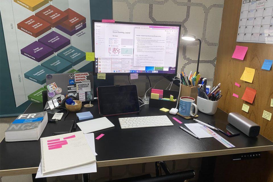 Foto de uma mesa, com monitor, teclado, mouse e notebook fechado, de pé, uma série de papéis e outros pequenos objetos. Na parede à direita, de madeira, vários post-its.