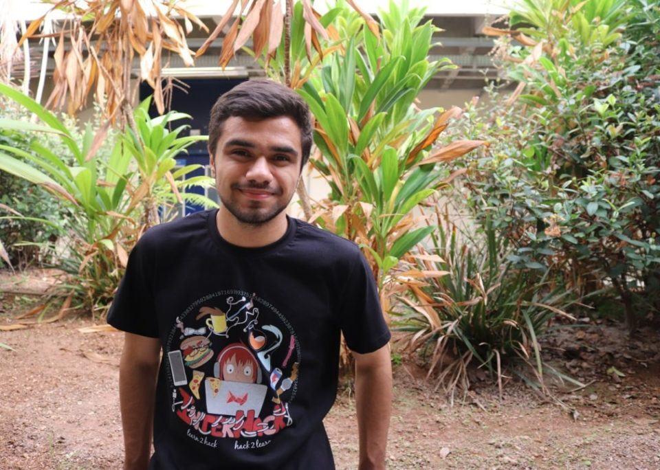 Homem de cabelo e barba curtos vestindo camiseta preta com ilustração no peito, de pé em frente a várias plantas.