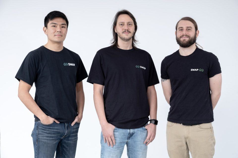 Três homens de camisetas pretas, lado a lado, em um ambiente claro.