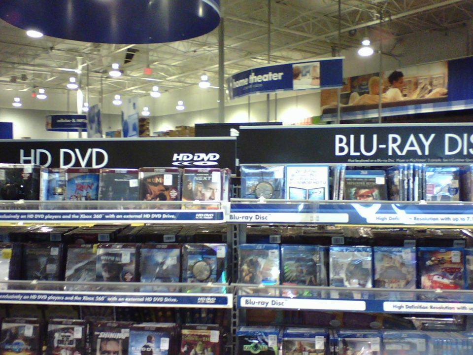 Prateleiras de uma loja exibindo discos HD DVD (esquerda) e Blu-ray.