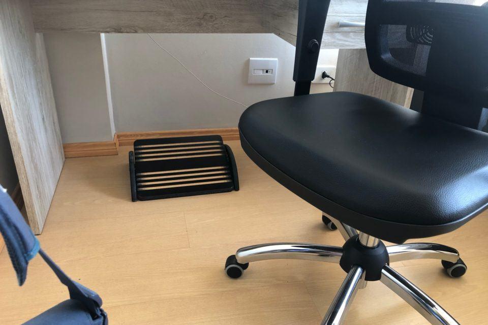 Chão, embaixo da mesa, mostrando o apoio para os pés. Ao lado, os pés e assento da cadeira.