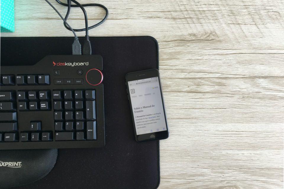 Foto de cima, com o iPhone 8 no centro, na borda do mousepad. À esquerda, parte do teclado e alguns fios saindo dele.