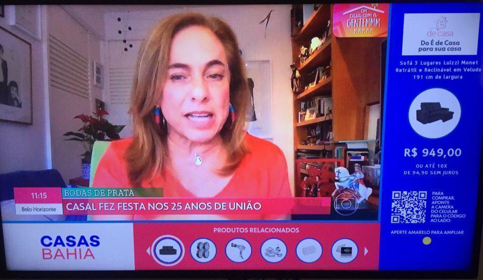 Foto de uma TV exibindo o programa É De Casa, com a interface do Ginga na lateral direita e parte inferior mostrando a oferta de um sofá.