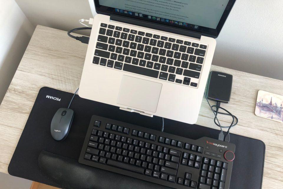 Foto de cima, mostrando teclados (do notebook e o mecânico), mouse, HD externo e mousepad.