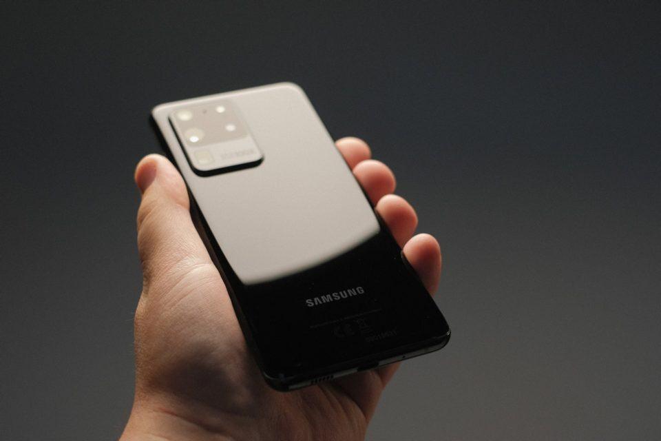 Mão segurando um Galaxy S20 Ultra em um ambiente escuro, com uma luz sobre o aparelho.