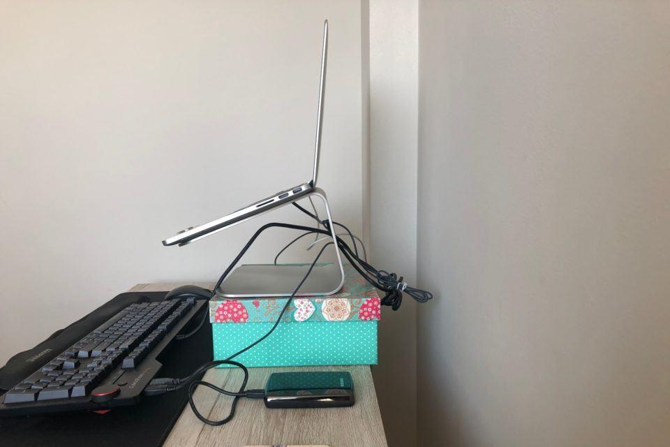 Foto de perfil do notebook, com vários fios enrolados atrás do suporte.