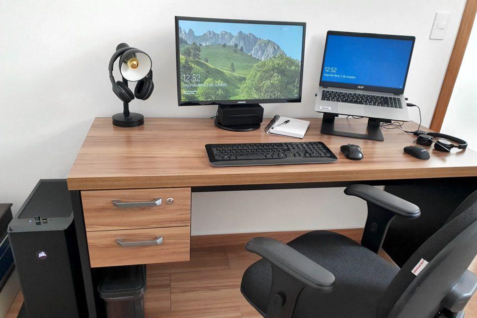 Mesa e cadeira, com monitor e notebook em suporte ao lado, luminária e fones de ouvido. À esquerda da mesa, um computador desktop.