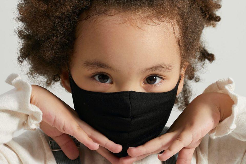 Retrato de uma menina usando uma máscara preta e com as mãos no queixo.