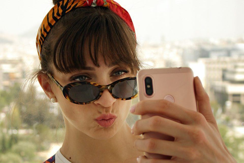 Close de uma mulher de óculos escuros fazendo duckface e segurando um celular à sua frente, presumivelmente tirando uma selfie.
