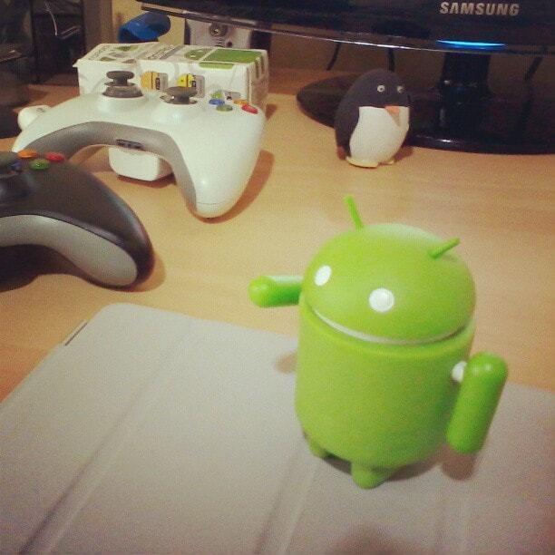 Foto de uma mesa, com o boneco do Android em primeiro plano e, ao fundo, um pinguim feito de ovo e dois controles de Xbox 360.