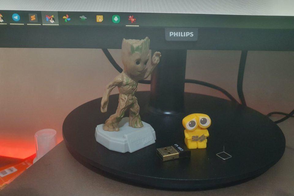 Dois bonecos, do Groot e do WALL-E, sobre a base de um monitor.