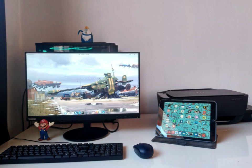 Monitor grande com um teclado, mouse e boneco do Mario à frente; atrás dela, um computador com personagem da Hora de Aventura em cima. À direita, iPad com a tela ligada e uma impressora preta ao fundo.