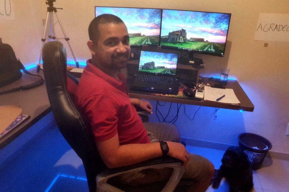 Homem de barba e cabeça raspada sentado em uma cadeira gamer, de lado, olhando para a câmera. Ao fundo, mesa com dois monitores grandes e um notebook entre eles, e várias coisas espalhadas sobre.
