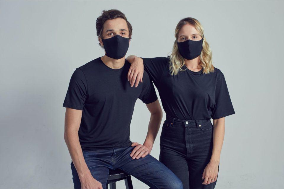 Homem e mulher, ambos de calça jeans, camiseta preta e máscara preta, olhando para frente. Homem sentado em um banco e mulher com o braço direito escorado nele.