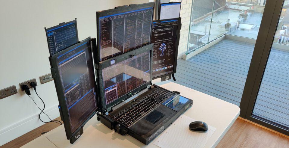 Literalmente um notebook com sete telas sobre uma mesa — duas frontais, duas em cada lado e uma pequena no apoio do pulso, perto do teclado.