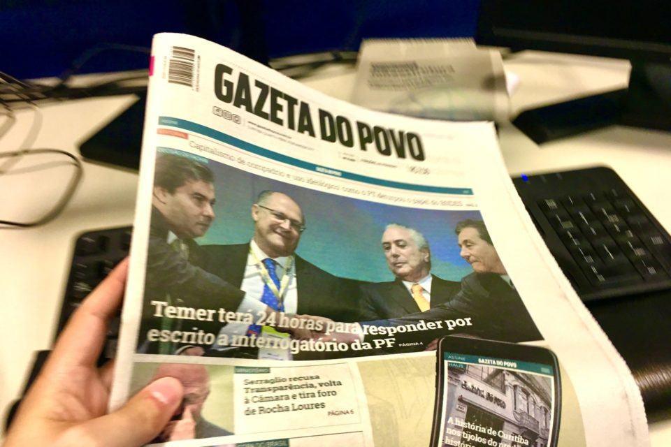 Foto de uma edição impressa da Gazeta do Povo segurada por uma mão.