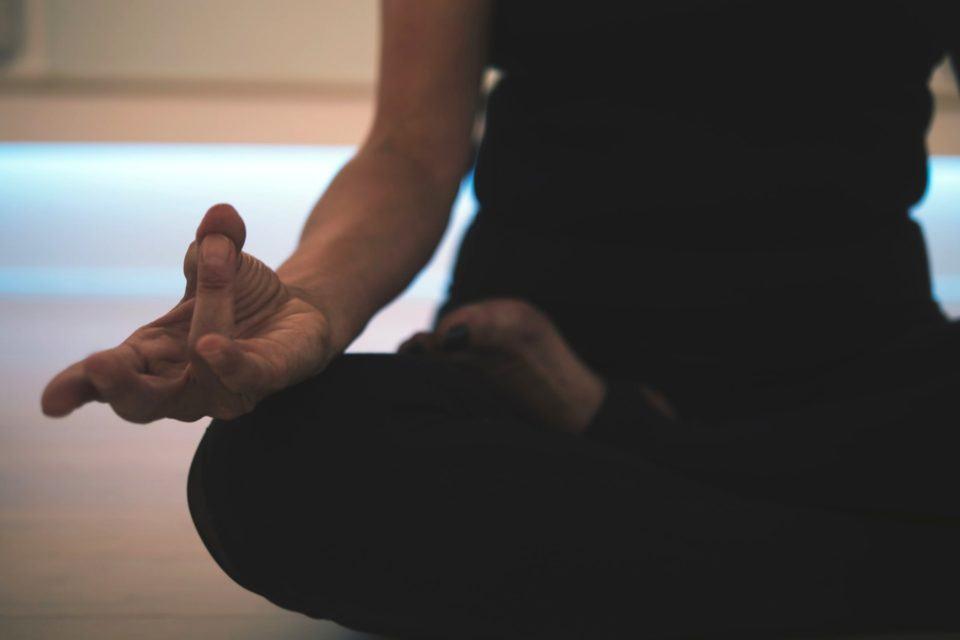 Detalhe na mão direita de uma pessoa, não identificada (a foto corta na altura do peito) praticando meditação.