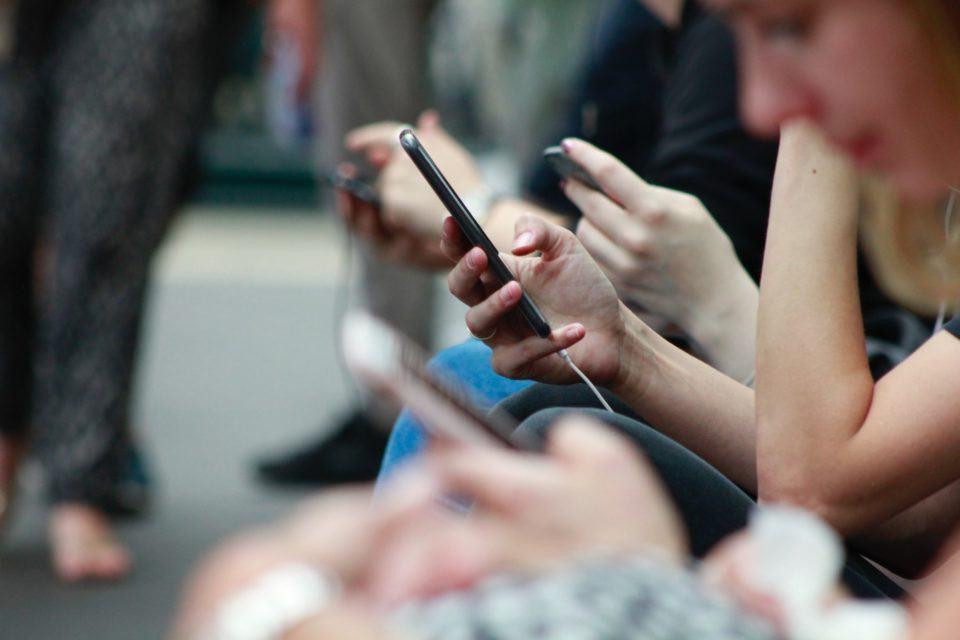 Várias mãos de pessoas enfileiradas segurando/mexendo em celulares.