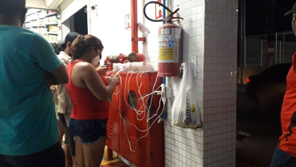Pessoas próximas a uma parede com tomadas, e vários celulares conectados a elas, sobre caixas vermelhas de extintores de incêndio.