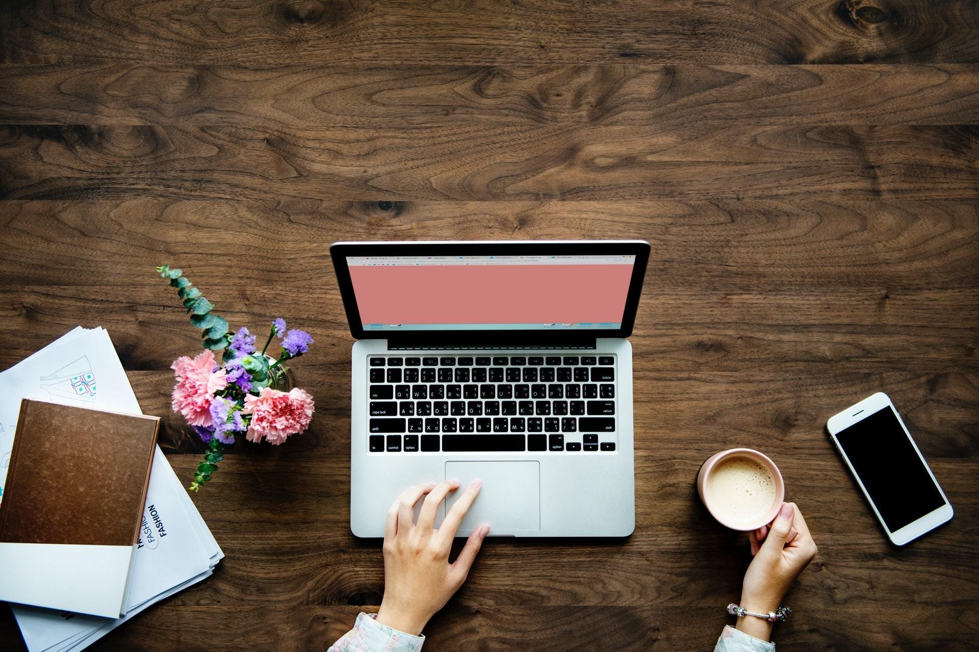 Foto de cima de uma mesa, com mãos mexendo em um computador e segurando uma xícara de café. Nas laterais, um celular e alguns livros.