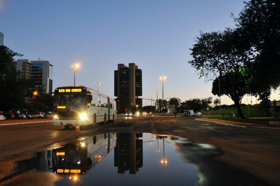 Foto de uma rua ao entardecer, com um ônibus passando. Ao fundo, o prédio do Banco Central, em Brasília.