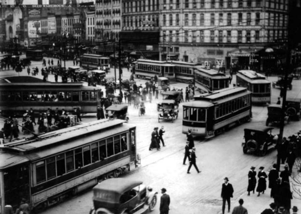 Uma rua de Detroit em 1917, com pessoas nas ruas disputando espaço com carros e bondes.