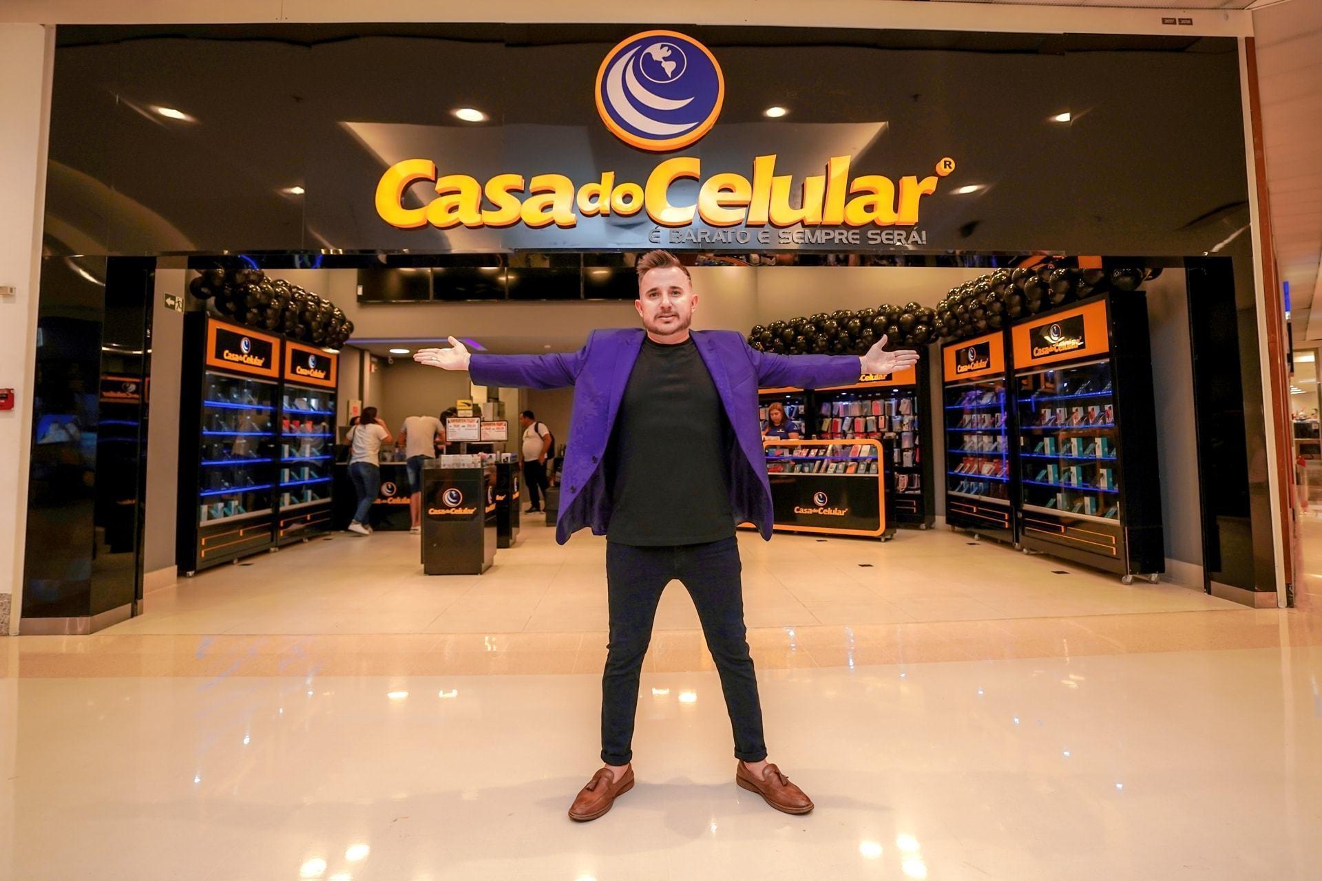 """Homem de roupa preta e terno roxo, braços abertos, em frente a uma loja de celulares com o letreiro """"Casa do Celular"""" acima."""