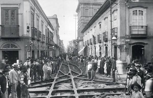 Uma rua de São Paulo, em 1902, com trilhos e pessoas.