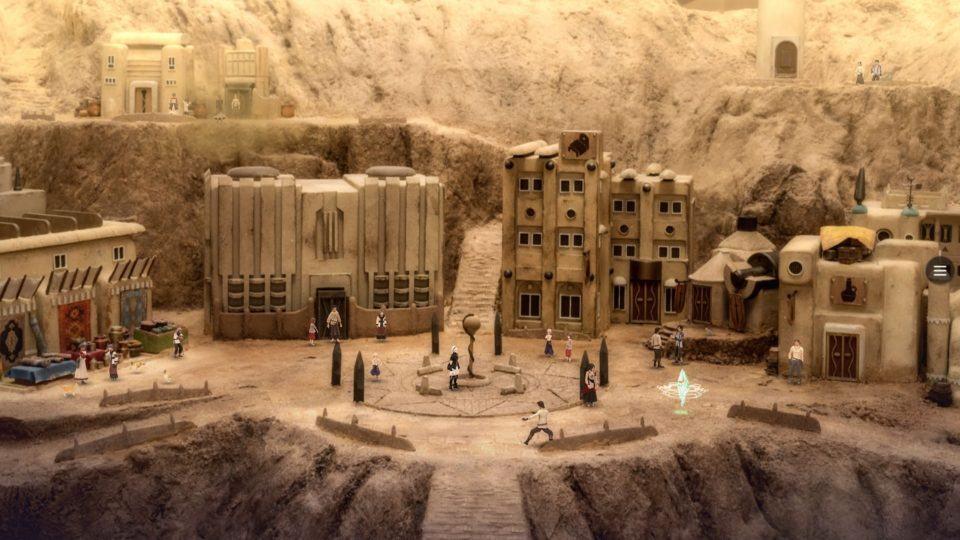 Diorama de um pequeno vale arenoso com algumas construções e bonecos digitais inseridos.