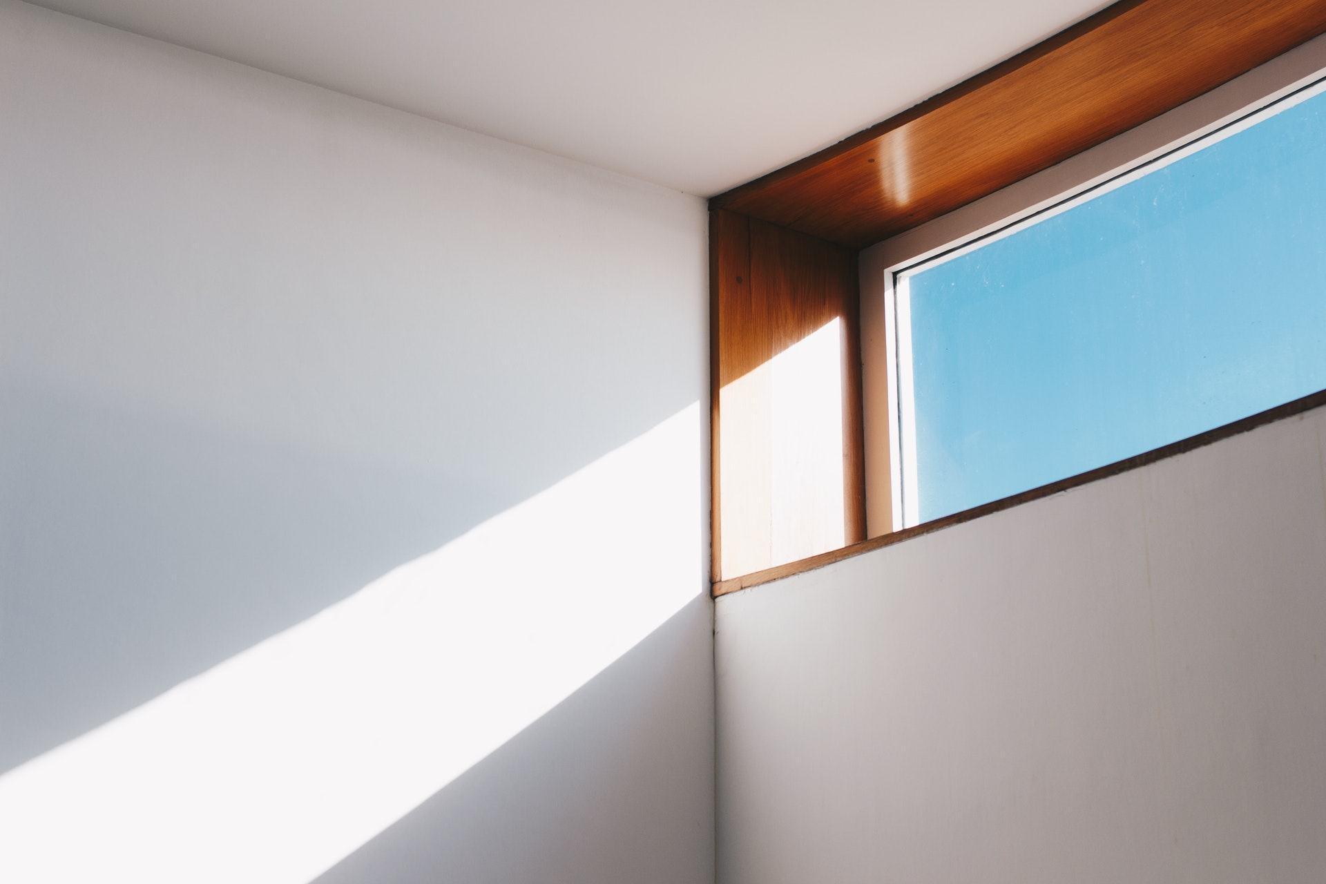 Feixe de luz solar passa por uma janela e bate na parede branca. A janela tem moldura de madeira e, lá fora, aparece o céu azul.