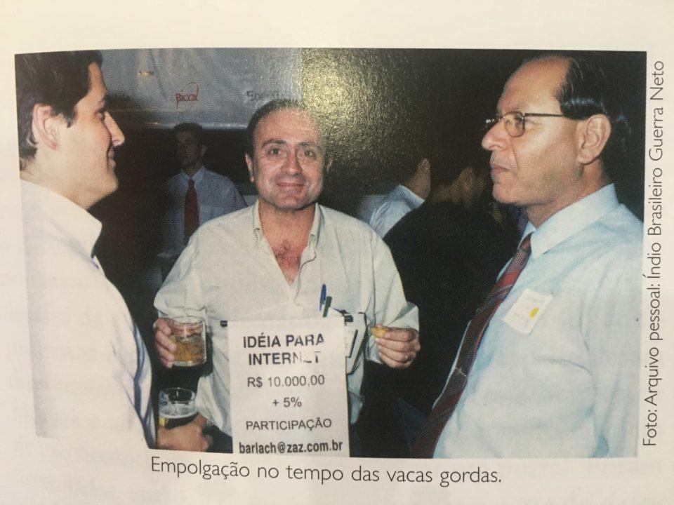 """Foto da foto. Três homens aparece, o do meio com uma placa no peito escrito: """"Ideia para internet: R$ 10 mil + 5%"""", seguido de um endereço de e-mail. Ele segura um copo de uísque e um canapé."""