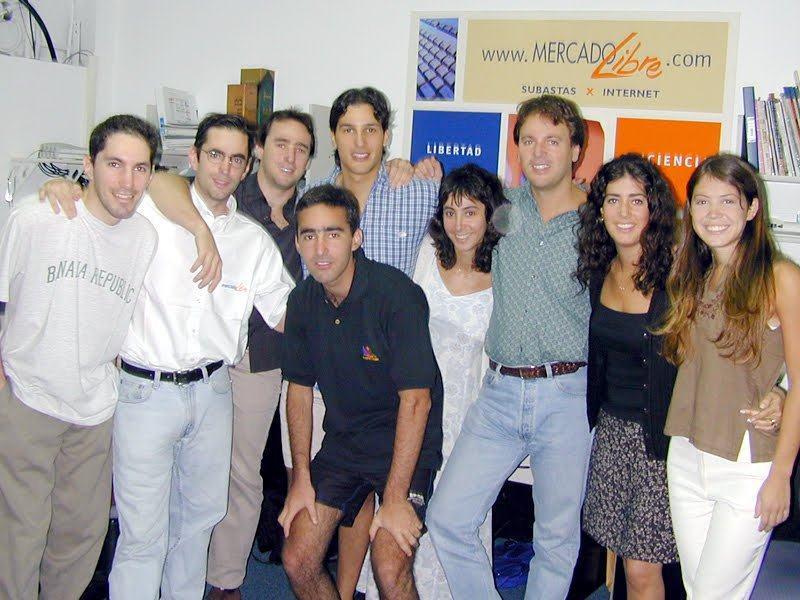 Grupo de pessoas posando para uma foto; homens de caça jeans e camisa, mulheres (três) de roupa social.